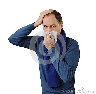 Man blowing his nose and holding his head