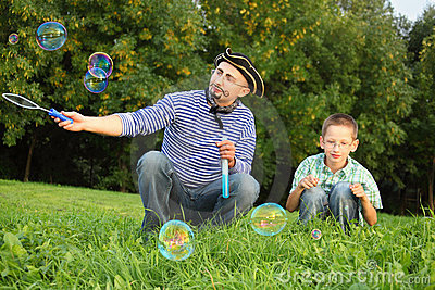 Man is blowing soap bubbles, his son is looking