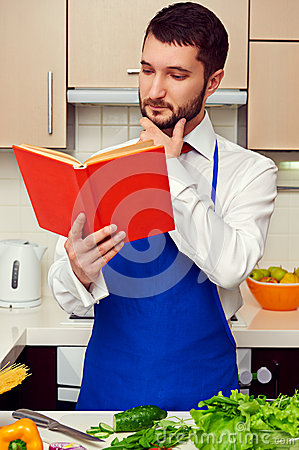 Man in blue apron reading cookbook
