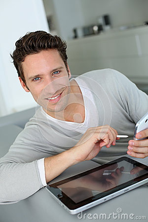 Man with blue eyes sitting in sofa and using tablet