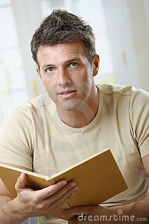 Man with book looking at camera