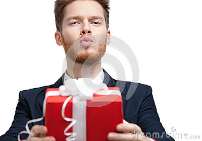 Man in bow tie offers a present and blows a kiss