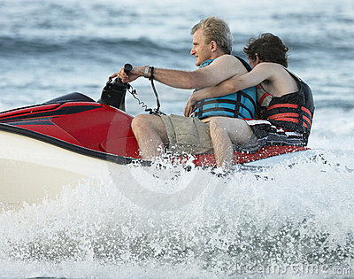 Man and Boy jetskiing in sea