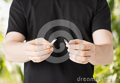 Man breaking the cigarette with hands