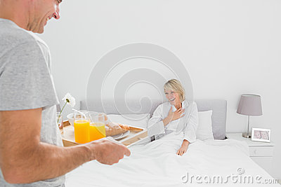 Man bringing breakfast in bed to his partner