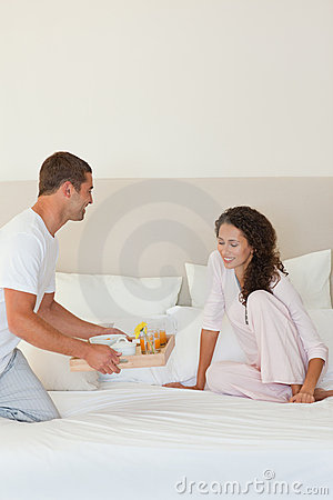 Man bringing the breakfast to his wife