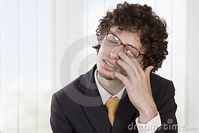 Man in business suit massaging his eye to relieve