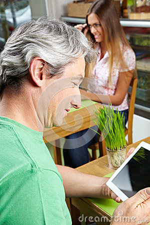 Man in café looking at tablet