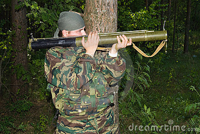 Man in a camouflage shoots from a grenade launcher