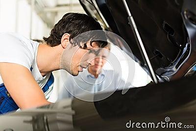 Man and car mechanic looking beneath a hood