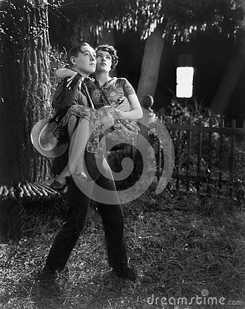 Free Man Carrying A Woman In His Arms Through A Backyard Stock Photography - 52023152