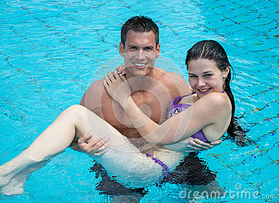 Man carrying girl at swimming pool.