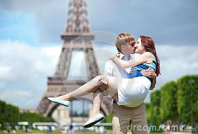 Man carrying girlfriend in his arms in Paris