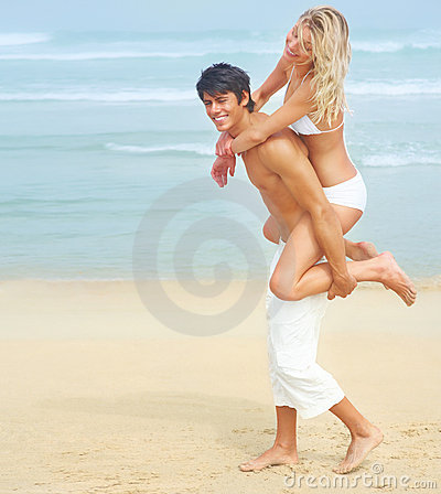Man carrying his pretty girlfriend on his back