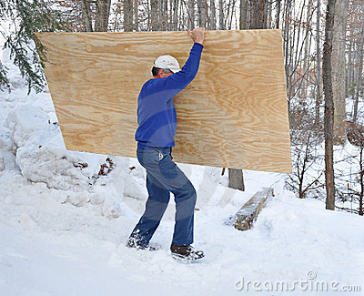 Man carrying plywood through snow
