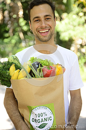 Man carrying recycle paper bag full of organic vegetable and fruits.