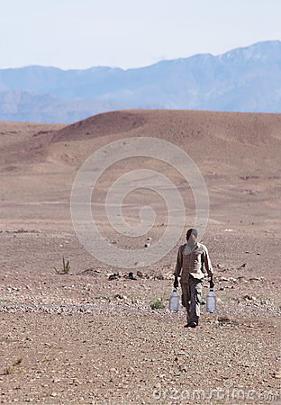 Free Man Carrying Water Through Desert Stock Photography - 92893292