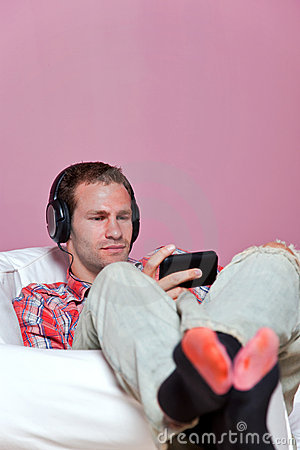 Man in casual clothing sat listening to music