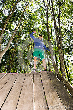 Man Celebrating Success After Climbing Wooden Slope