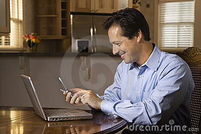 Man with Cell Phone and Laptop