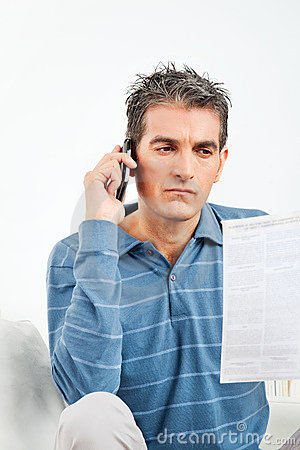 Man with cell phone and phone bill