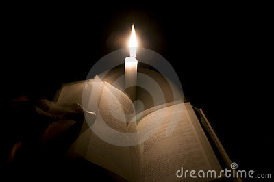 A man changes bible pages in front of a candle