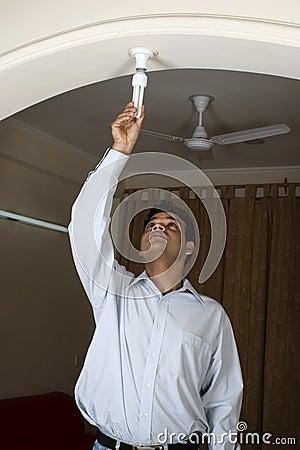 Man changing bulb to CFL