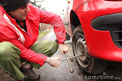 Man changing a tire on the street