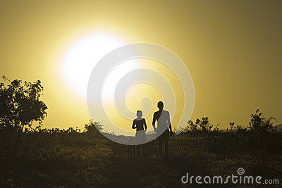 Man and child with dog at sunset