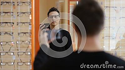 Man choosing new pair of glasses at optometrist stock video