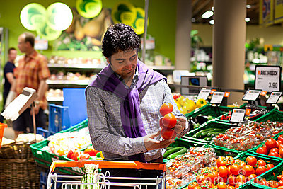 Man choosing tomatoes in a fresh food section