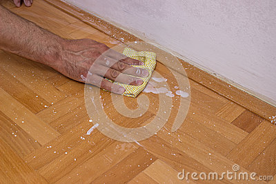 Man cleaning floor after painting wall