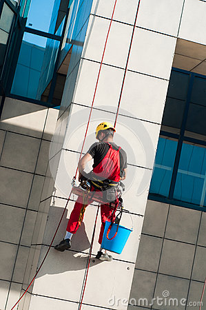 Free Man Cleaning Office Building Hanging On Ropes Stock Images - 70235374