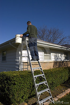 Man Cleaning Rain Gutters Inspecting House Roof Royalty