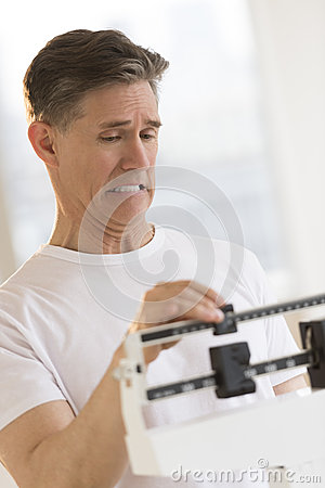 Man Clenching Teeth While Using Balance Weight Scale