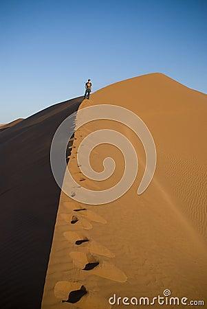 Man climbing sand dune