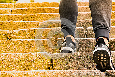 A man climbing the stone steps to success Stock Photo