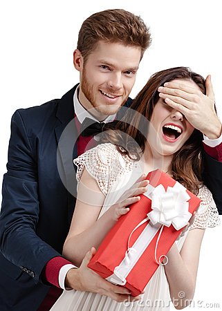 Man closes eyes of his girlfriend presenting a gift