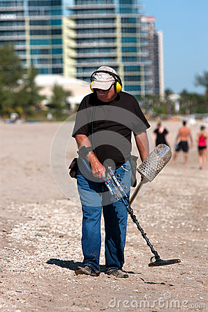 Free Man Combs Beach With Metal Detector Stock Photo - 30166390