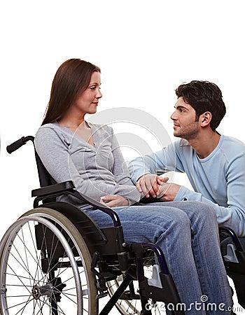 Man comforting woman in wheelchair