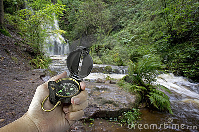 Man with compass near waterfall