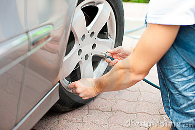 Man is controlling the tire pressure of his car