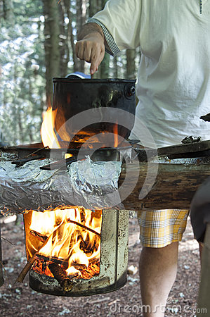 Man cooking dinner on campfire