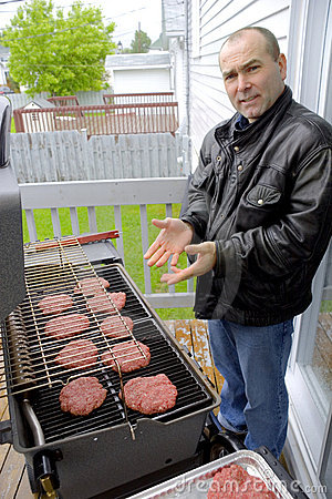 Man cooking hamburgers on a BBQ