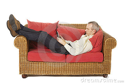 Man on a couch with an e-reader.