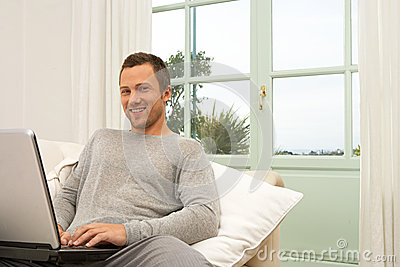 Man on couch with laptop at home.