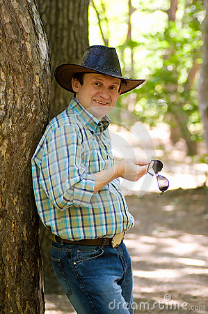 Man with cowboy hat in the forest