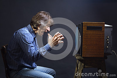 A man cries while watching TV.