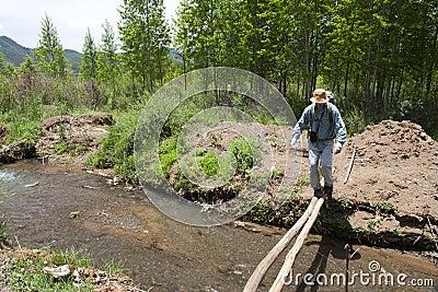 Man Crossing Flimsy Bridge