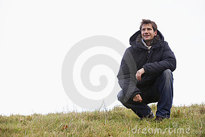 Man Crouching In Park